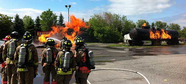 Toronto firefighters demonstrating how to put out a fire on a train transporting chemicals.
