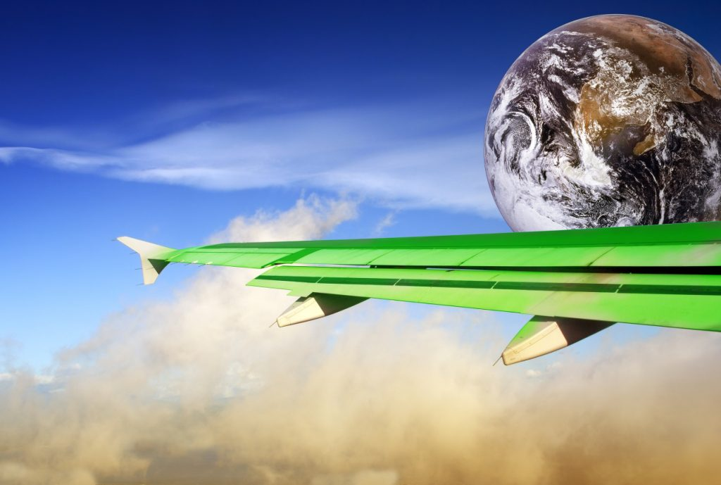 Globe with green airplane wing flying over a tropical cloudscape. Metaphor or concept of energy conservation and more efficient flying in the aviation industry to save energy and reduce CO2 output in order to combat global warming.